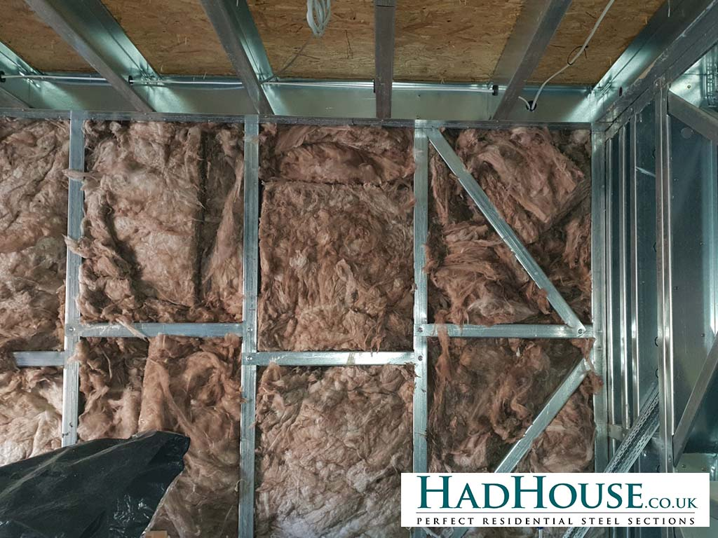 Mineral wool is packed between the studs to add to the insulation properties of the building